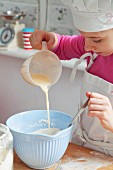 A girl pouring milk into a bowl of flour