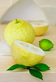 Lemons, whole and halved, with lemon leaves and a lime