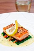 Pan-fried salmon on white wine sauce with vegetables