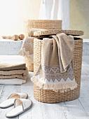 Wäschekorb mit abgelegtem Handtuch neben Badeschlappen und Handtuchstapel auf weißem Dielenboden