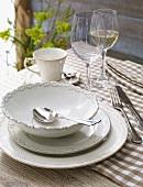 Tafelgedeck mit Suppenteller und Weingläser auf karierter Tischdecke