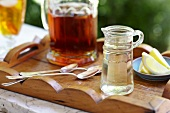 Small Glass Pitcher of Simple Syrup; Lemons and a Pitcher of Iced Tea; On a Tray Outdoors