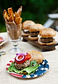 A grilled buffalo burger in a wholemeal bun on a cardboard plate decorated with a US flag