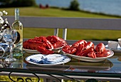 Platters of Cooked Lobsters on an Outdoor Table; White Wine