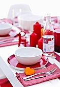 A table laid for Christmas in red and white with a small felt heart