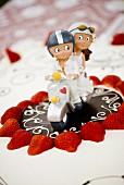 A decorative bridal couple on a wedding cake