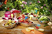 Vegetables and fruit in small bowls on a table outdoors