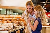 Mutter und Tochter kaufen Brot im Supermarkt