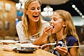 A mother and daughter eating sushi with chopsticks