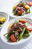 Salad with tomatoes, French green beans, red onion and oil.