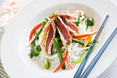 Seared Tuna steaks on rice noodles with shredded vegetables and Thai sauce