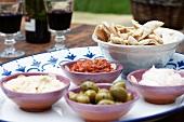 Verschiedene Dips, Oliven & Pitabrot auf Tisch im Freien