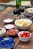 Dips, Chips, Oliven, Feigen, Tomaten & Rotwein auf Tisch im Freien