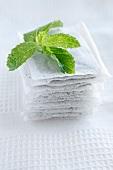 Mint leaves on mint tea bags on white tea towel