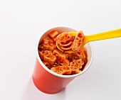 Pasta in bolognese sauce in a cup with a plastic spoon
