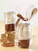 A jar containing the dry ingredients for making hot chocolate with marshmallows