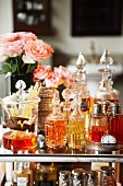 Perfume bottles, room fragrance diffuser and vases of roses on glass table top