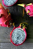 Whole and halved red dragon fruit (view from above)