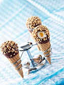 Vanilla ice cream in waffle cones with caramel sauce and chocolate and nut coating