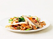 Grilled turkey strips on a bed of soba noodles with vegetables