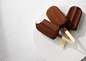 Three ice lollies coated in chocolate