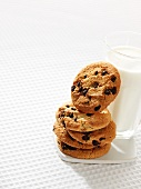A stack of chocolate chip cookies next to a glass of milk