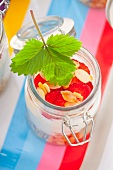 A jar containing ingredients for muesli: rolled oats, vanilla yoghurt and strawberries