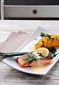 Gegrillter Lachs mit Rosmarin und Zitronensauce, serviert mit gelbem Risotto