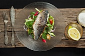 Nile perch on a bed of salad, with lemon and sea salt