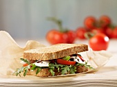 A wholegrain bread sandwich filled with tomatoes and mozzarella