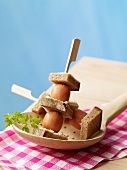 Skewers of mini bockwurst sausages with bread and butter