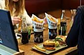 Zwei junge Frauen essen Burger mit Pommes frites und trinken Cola