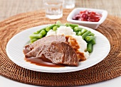Slices of roast beef with mashed potato and green beans