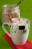 White hot chocolate with marshmallows in a mug, with dry ingredients for making it in the background