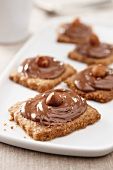 Cappuccino biscuits topped with chocolate and hazelnut spread and hazelnuts