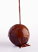 A chocolate ball being coated in glaze