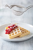 Waffles with redcurrants being dusted with sugar