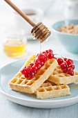 Waffles with redcurrants being drizzled with honey
