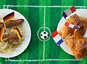 Sausages with cabbage (Germany) and croissants (France) with football-themed decoration