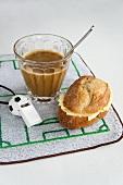A breakfast of coffee and a bread roll with football-themed decoration