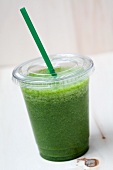 A green smoothie made with spinach, lamb's lettuce, apple, banana and apple mint in a plastic cup