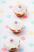 Three mini cupcakes decorated with sugar icing and marzipan balls