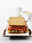 Wholegrain bread sandwich filled with corned beef and pickled gherkins