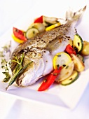 A whole gilt-head bream with vegetables