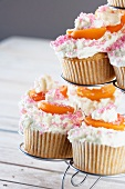 Cupcakes in a stand topped with cream, apricots and sugar sprinkles