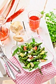 A spring salad of asparagus, rhubarb and rocket on a table outdoors