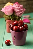 A still life featuring fresh cherries and an arrangement of roses