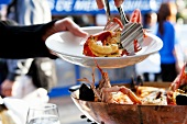 Serving Lobster From a Wooden Bowl with Tongs at an Outdoor Restaurant in the South of France