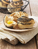 Poppy seed rolls with butter on cream linen napkin
