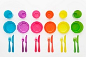 Colourful plastic plates, cups, bowls and cutlery